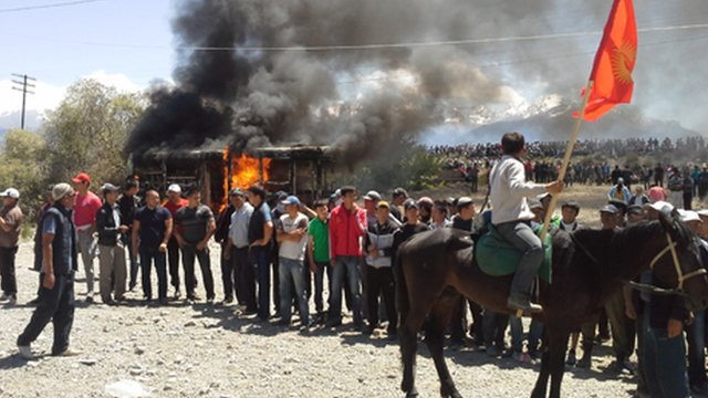 A bus burns as protestors blockade the Centerra gold mine in Kyrgyzstan (BBC)