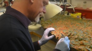 Jersey Heritage Trust conservator Neil Mahrer works on separating a coin from the massive Grouville Hoard