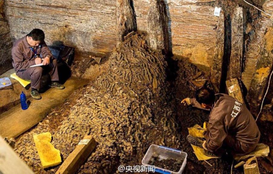 Researchers sift through huge piles of the copper coins. Source: ecns.cn