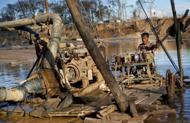 A man operates a makeshift rig used for illegal gold mining.
