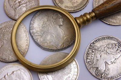 Old-fashioned magnifying glass laying on old silver coins